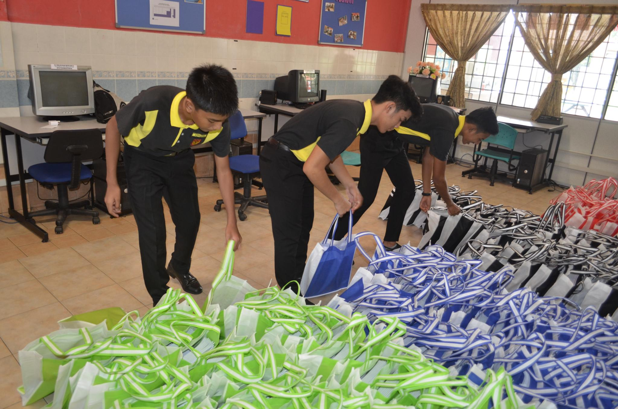 The school's Prefects preparing bags full of exercise books.